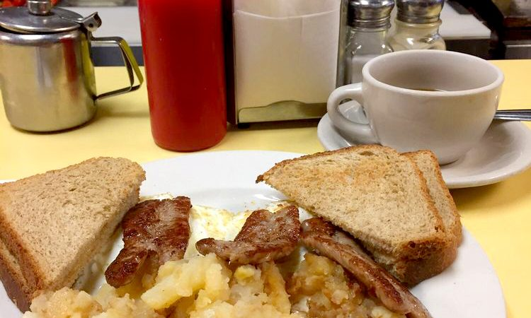 2 Egg platter w Sausage. This picture depicts an order of two eggs Fried with on fried potatoes, sausage and Toast cut in half on top of a platter with a cuppa coffee on the side, served on Johnny's counter tap