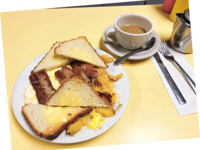 2 Eggs Any Style Platter. This picture D pics a platter with scrambled eggs home fried potatoes and sliced toast on top of a white platter served on Johnny's yellow counter. It also shows a side order of sausage that is usually an additional charge