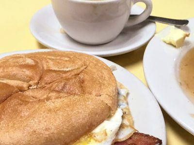 2 Eggs and bacon on a Roll. This picture depicts sandwich that consists of two fried eggs with bacon served on a Kaiser roll that is cut in half on top of a white plate on Johnys yellow countertop