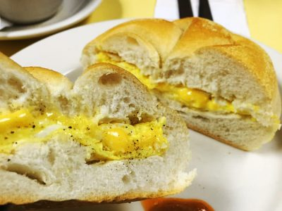 2 Eggs on a Roll w cheese. This picture depicts an egg sandwich that consists of two eggs and American cheese scrambled served on a Kaiser roll that is cut in half on top a white plate Served on Johny's yellow counter with a cup of coffee on the side