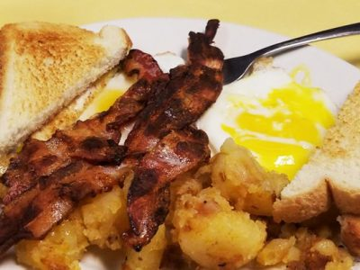2 egg platter with bacon. This picture depicts two sunny side up eggs Served with home fried potatoes on the side, topped with three pieces of bacon and two slices of toast cut in half placed on top.