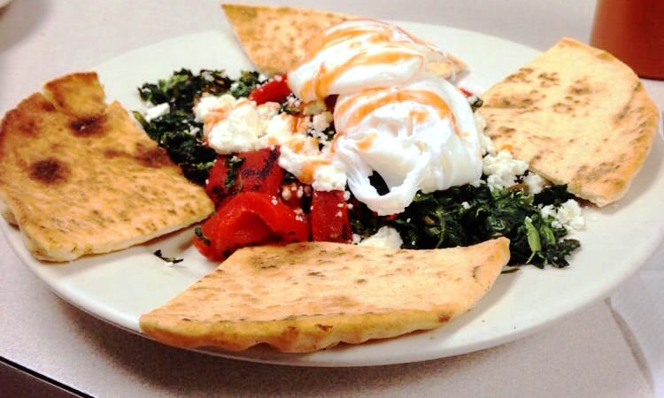 Aidans Way. This picture did pics two poached eggs served on top of a bed of sautéed spinach and roasted peppers, accompanied with a toasted pita cut into four triangular pieces on top of a plate Served on Johny's original white counter