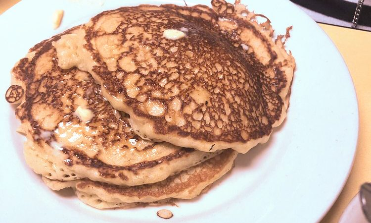 Banana Pancakes. This picture depicts an order of banana pancakes which consists of three slices of Johnny's pancakes one on top of the other with butter on the side Served on a white plate on top of Johnys yellow counter