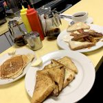 Bigman Breakfast. This picture shows three separate platters that consists of Pancakes, eggs, Bacon, sausage, and home fries on Johnys counter.