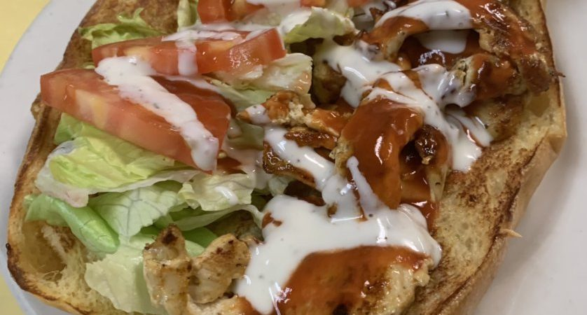 Buffalo Chicken Sandwich. This picture depicts grilled chicken chopped and served on an open faced semolina hero with lettuce tomato spicy hot sauce and ranch dressing drizzled all over served on top of the white plate on Johnny's