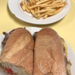 Cheese Steak Hero. This picture depicts a sandwich that consists of sliced steak, peppers and onions, and melted American cheese on a sub that is cut in half served on a white platter accompanied by a side of french fries for an extra charge on top of Johnys counter