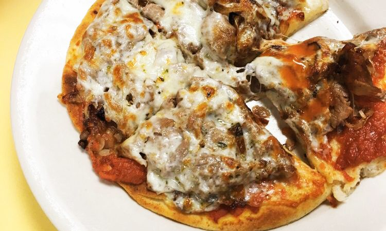 Cheesesteak Pizza. This picture depicts sliced steak with sautéed onions and tomato sauce on a pita bread which represents somewhat of a personal pizza served on a white platter on Johnys countertop