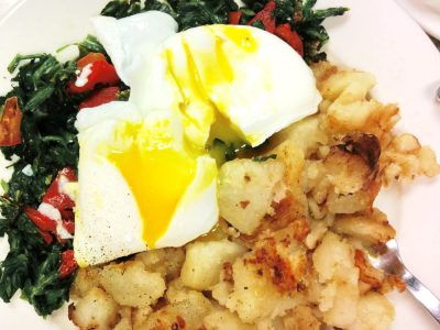 Emmas Eggs. This picture depicts two poached eggs on top of a bed of sautéed spinach and roasted peppers with an additional water of home fries accompanied on the side for an extra charge, served on a weekly