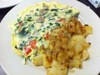 Farmers Omelette. This picture depicts an omelette that is consisted of spinach, mushrooms, tomato and onion with home fried potatoes on the side served on a white plate on Johnny's counter top