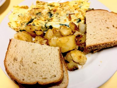 Florentine Omelette. This picture depicts the omelette that consists of spinach and feta cheese accompanied by home fried potatoes and toast served on a white platter on Johnys counter top