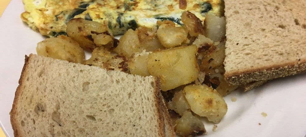 A picture of Eggs Florentine has spinach toast and home fries. Yum.