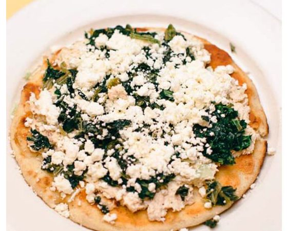 Great Alexander. This picture depicts an order of fresh tuna salad that is topped with spinach and feta cheese served open face on a pita bread that is on a white platter served on Johnys countertop