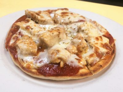 Grilled Chicken Pizza Pita. This picture depicts grilled chicken chopped up and served on a pita bread with tomato sauce and melted mozzarella cheese on a white platter which is on top of Johnny's counter top