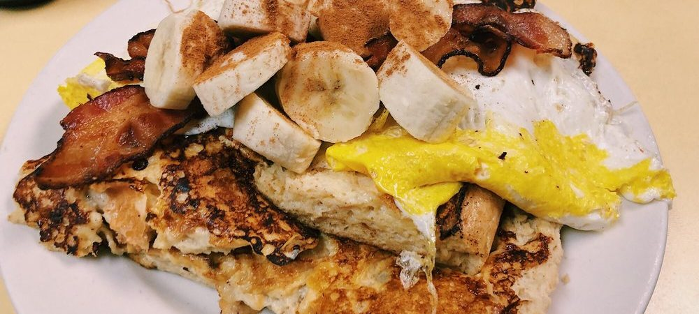 King Kong French toast. This picture depicts French toast made out of eight sub roll that is dipped into the batter. This picture contains the French toast itself topped with Fried eggs, Sliced bananas topped with bacon and ground cinnamon