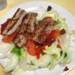 House salad. This picture is the pics a salad that consists of lettuce, tomato, roasted peppers, onions, Kalamata olives on a white plate served with Sausage on top which is an additional charge.