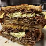 Mr. Moses. Just picture Depicts hot roast beef, homemade coleslaw and melted cheddar cheese on grilled Ryebread that is stacked up one on top of each other on a white platter served on Johnys Luncheonette counter