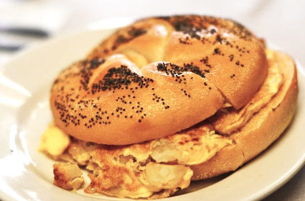 Potato and Egg on a Roll. This picture depicts a sandwich that consists of egg and potato combined, on a Kaiser roll that is cut in half on top of a plate Served on Johny's's counter top