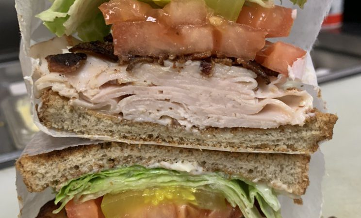 Turkey Club Sandwich. This picture depicts a sandwich that consist of sliced turkey, lettuce and tomato, Bacon Served on Sliced and Toast that is cut in half and placed one on top of another.