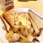 Western Omelette. This picture depicts an omelette which consists of chopped ham, peppers and onions served with home fries potatoes on the side and two slices of toast on top, served on a white planter on Johnny's counter top