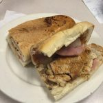 Cubano sandwich. This picture depicts an order of grilled chicken, grilled ham and Swiss cheese and pickles on a pressed sub that is cut in half on top of a white platter on Johnny's original counter top
