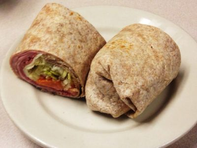 basic wrap sandwich. This picture to pics a basic wrap sandwich that would usually be served on a whole wheat were playing rap that consists of a wide array of meats veggies and cheeses. It is cut in half and served on a white bladder on Johnny's original Counter top