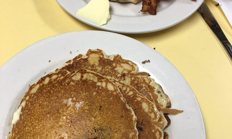 pancakes. This picture indicates an idea of what the pancakes and Johnys Luncheonette look like when you eat it in. It is a picture two orders of pancakes on Johny's yellow counter