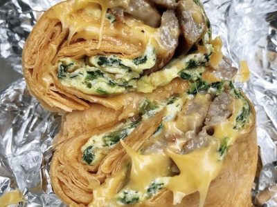 Spinach Egg Sausage and Cheese Wrap. This picture depicts a rap that consists of Two eggs, spinach, sausage and melted cheese that is cut in half ends Served open face on a piece of take out aluminum foil