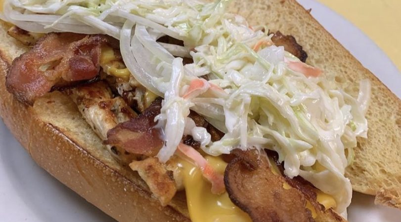 Sloppy Johny. This picture he picks a sandwich on a sub/hero with grilled chicken, raw onion, American cheese, crispy bacon and homemade coleslaw swerved on a white plate on Johnys yellow countertop